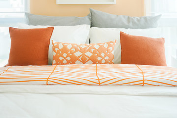 Modern bedroom interior with roll of orange, white and gray pillows on bed