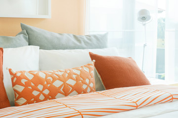 Orange, white and gray pillows on bed in modern bedroom interior
