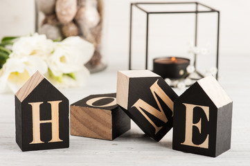 Flowers and lit candle, wooden letter Home