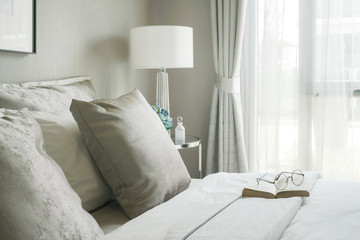 Glasses and book on comfortable bed in modern interior bedroom