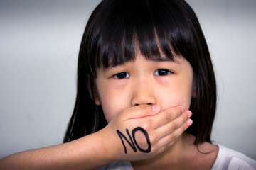 Child with Hand Over the Mouth with 'No' on the hand