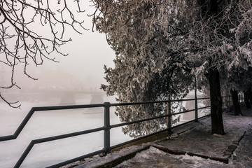 foggy morning near the bridge through the frozen river