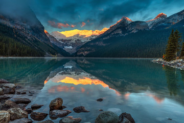 The First sunlight illuminating Victoria glacier on a calm morning in Autumn at Lake Louise in Banff National Park, Alberta, Canada.  Wall mural