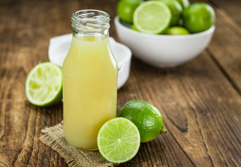 Fresh Lime Juice on wooden background (selective focus)