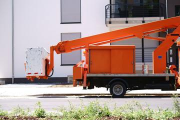 Hebebühne / Eine Hebebühne an einem kleinen Lastwagen steht vor einem modernen Wohnhaus.
