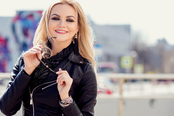 Trendy girl portrait outdoor. A walk in the city, laughs and enjoys walks