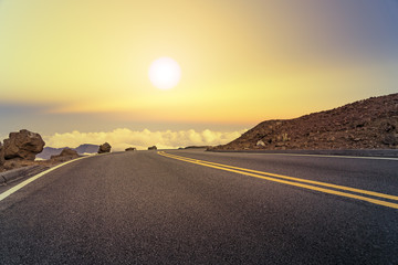 Mountain road above the clouds at sunset