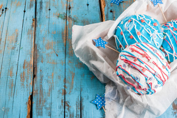 Food for independence day. 4th of July. Festive breakfast: American donuts with glaze in colors of USA flag blue, red, white. On light blue old rustic wooden table. Top view copy space