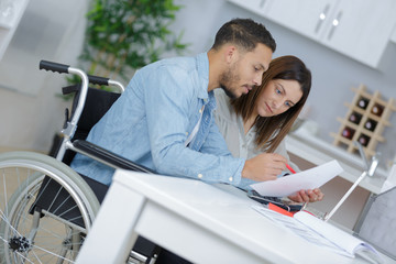 couple at home reading document, man in wheelchair