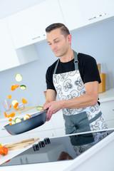 manpreparing vegetables on the frying pan