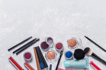 brushes, pencils, lipsticks,eyeliner,eye shadow, hand cream, with the edge from the photo below, brown background, close-up, copyspace, beauty, makeup