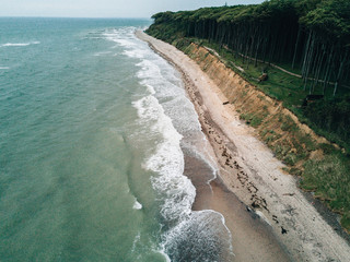 Aerial photo of coastline on a stormy day hitting a beach cliff overlooked by a forest