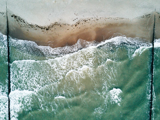 Aerial photo of waves on a stormy day with beach