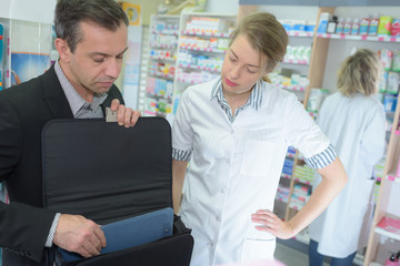 positive female pharmacist counseling customer