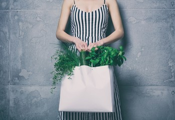 woman holding white bag with organic herbs