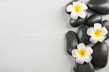 Spa stones with plumeria flowers on light background