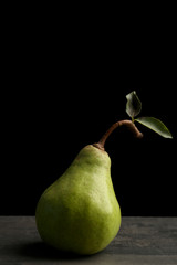 Fototapete - Green pear on black background