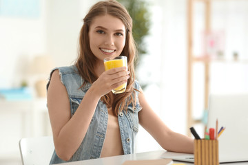 Weight loss concept. Beautiful young woman sitting at table and drinking healthy delicious smoothie
