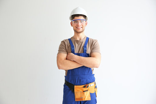 Smiling young electrician in hardhat and with glasses on white background