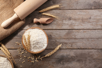 Composition with flour and kitchen utensils on wooden background