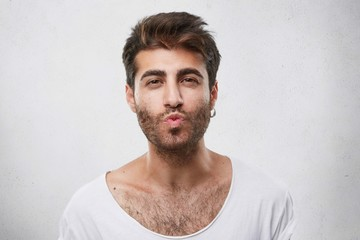 Lovely handsome guy flirting with girl blowing her kiss. Unshaved man with attractive appearance showing to his girlfriend sympathy going to kiss her. Macho man isolated over white background