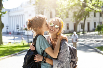 Two sisters having fun outdoors hugging and kissing each other showing their love to each other. Best friends meeting at campus. Restful women enjoying sunny weather while having walk outdoors