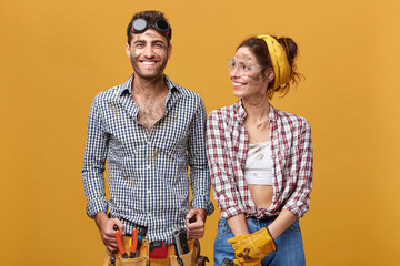 Two cheeful craftsmen enoying results of their work, standing next to each other with dirty but happy faces. Male and female electricians having a break while doing renovations in residential house Wall mural