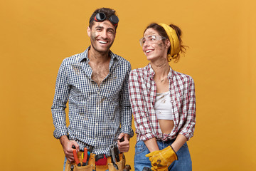 Cheerful female electrician or mechanic in protective gloves and goggles looking at her male colleague who is wearing belt kit with pliers, screwdriver, hammer and other tools needed for work Wall mural