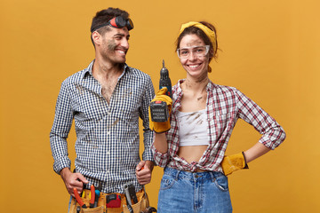 People, occupation, job, profession and relationships. Two young mechanics with dirty faces enjoying work together: man with belt kit of instruments looking with delight at his colleague holding drill