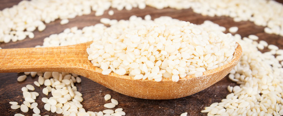 Sesame seeds with spoon on rustic board, healthy nutrition concept
