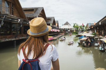 Young women travel at floating market in Thailand
