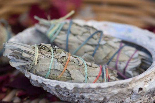 White Sage Smudge Sticks in a Seashell in a Basket with Rose Petals