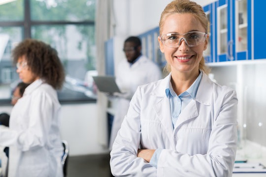 Portrait Of Smiling Woman In White Coat And Protective Eyeglasses In Modern Laboratory, Female Scientist Over Busy Researchers Team In Lab