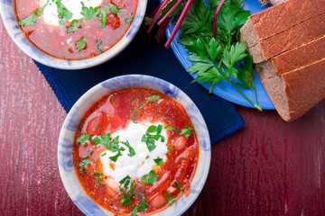 Ukrainian traditional borsch. Russian vegetarian red soup  in blue bowl on red wooden background.  Borscht, borshch with beet. Two plates. Top view.