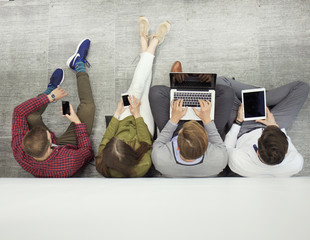 Group of attractive young people sitting on the floor using a laptop, Tablet PC, smart phones, smiling.