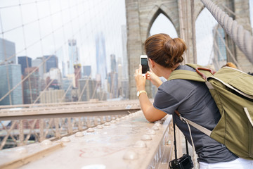 Tourist on Brooklyn bridge taking picture of scenery