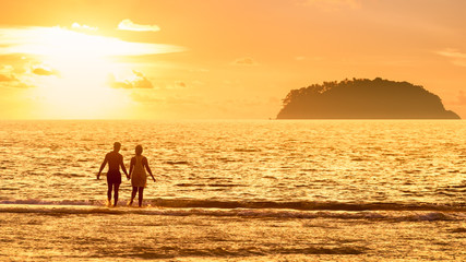 Silhouette of couple on the beach against sunset. Summer concept.