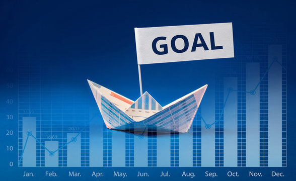 Goal word with Boat paper graph on blue ocean.Business concept.