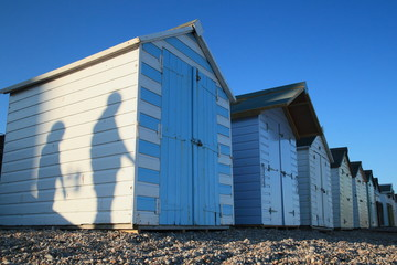 Shadows of people passing by beach huts in Seaton, Devon