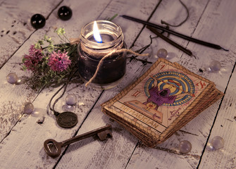 Black candle and old tarot cards on wooden planks