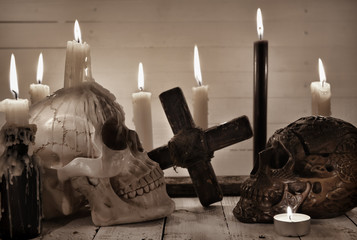 Still life with two scary skulls, black candle and cross