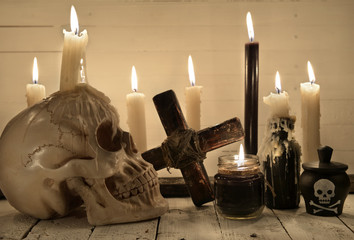 Scary still life with skull, burning candles and cross
