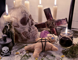 Voodoo still life with skull, doll and burning candles