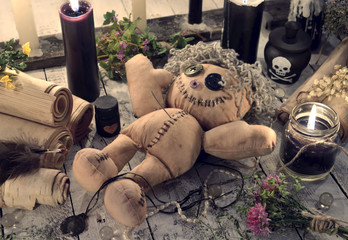 Scary voodoo doll with paper scrolls and black candles