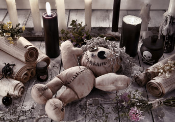 Voodoo doll with black candles and ancient scrolls
