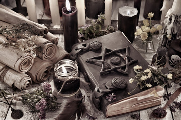 Black magic book with burning candles and ancient scrolls