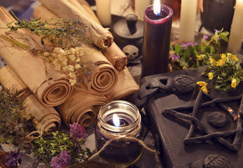 Black candles with old parchments and evil magic book with pentagram on cover