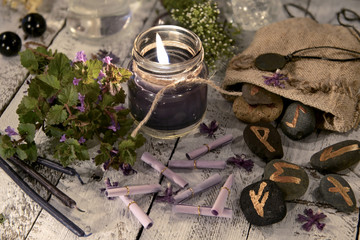 Fortune telling still life with black candle, runes and wish scroll