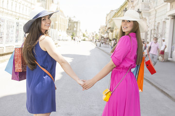 Two beautiful young cheerful women holding shopping bags and hands while looking at eachother.  Beautiful girls with shopping bags walking in a city center.