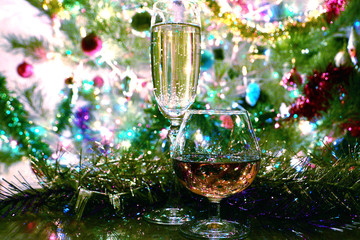 A glass of wine and strong alcohol on the background of a festive New Year's decoration